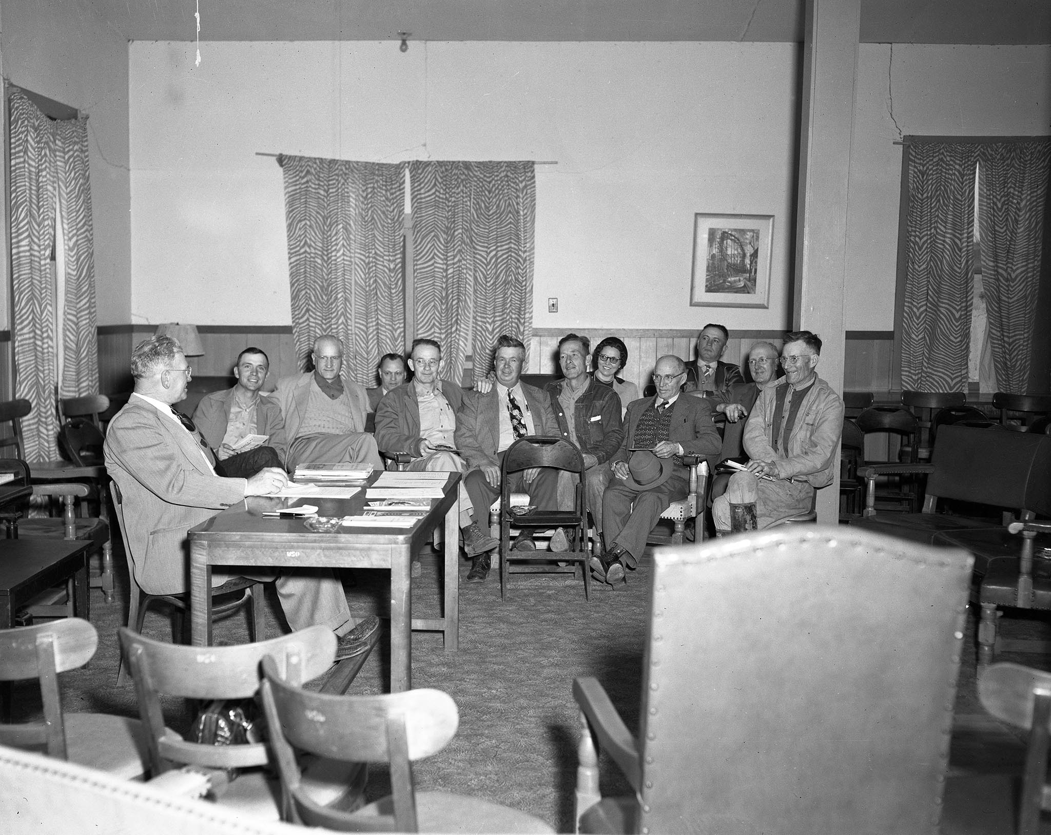 Early in 1952, every county Farm Bureau in Oklahoma was visited by state leaders in an effort to create more personal relationships between local members and the state organization. This photo was taken at one of the first conferences, which was held at the Hugo Community Center with Choctaw County Farm Bureau members. At the desk is Jack Norris, President of the Choctaw County Farm Bureau. In the background are (left to right) Lex Eddleman, John I. Taylor, Dan Arnold, Ernest Means, Clarence Adams, Glen Grubbs, Mrs. Eugene Jones, O.T. Eddleman, Mart Fowler, E.A. Kissick, and Rolly Morris.