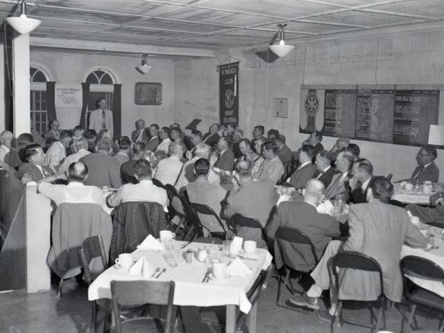 Kiowa County Farm Bureau meets for their annual public relations meeting on April 21, 1953, where the master of ceremonies, Kiowa County Farm Bureau President Alva Smith, introduces Oklahoma Farm Bureau President John I. Taylor as the speaker of the evening.