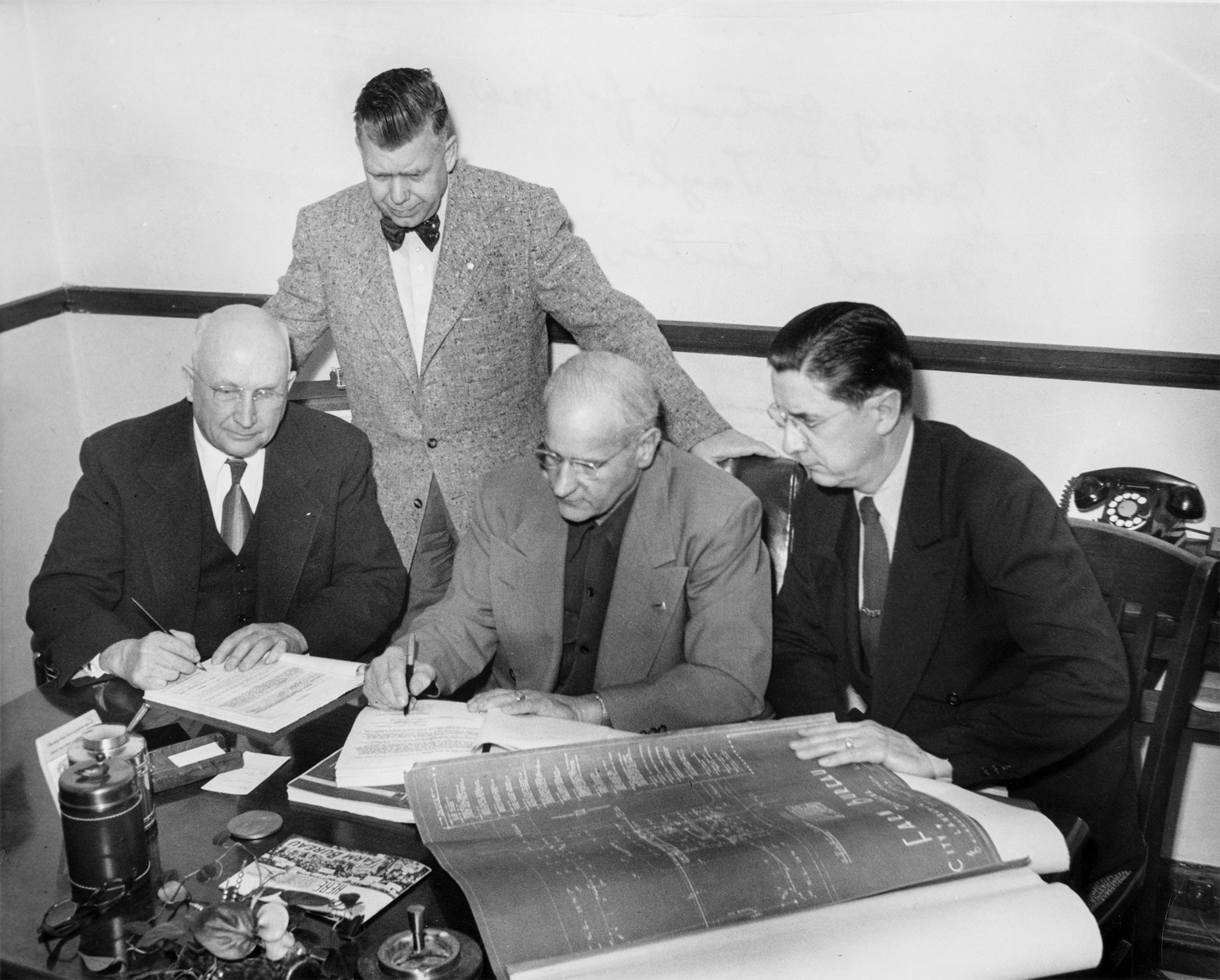 Oklahoma Farm Bureau recognized the need for a larger building to house the ever-expanding organization. On February 9, 1953, a contract was signed for construction of a new building near the Oklahoma State Capitol. Here, OKFB President John I. Taylor (seated center) signs the contract, while Charles M. Suttle, the contractor (left), signs another copy. Frank Carter (standing) and Martin Lawrence, architect, look on.