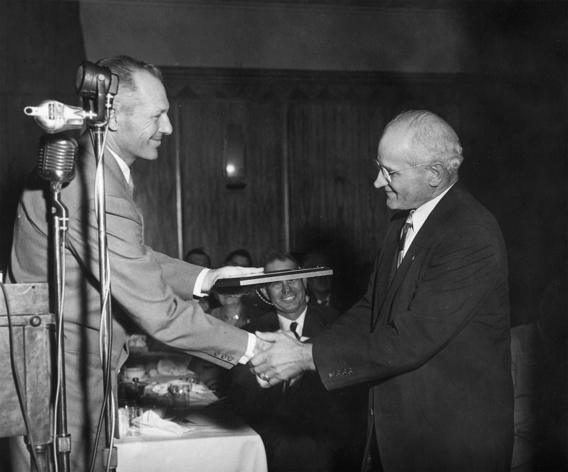 In August 1953, John I. Taylor resigned as president of Oklahoma Farm Bureau due to pressing family matters. In this photo, Taylor was honored with a plaque commemorating his 11 years of service and leadership to Farm Bureau, presented by OKFB Board Member Darrell McNutt at the 1953 convention. However, Taylor did not end his commitment to Farm Bureau with his resignation. In 1960, he was called to Washington, D.C., by American Farm Bureau Federation President Charles Shuman to serve as an assistant legislative director. In his new position, he visited several states, earning a reputation as a well-informed specialist on soil and water conservation among congressmen and associates.
