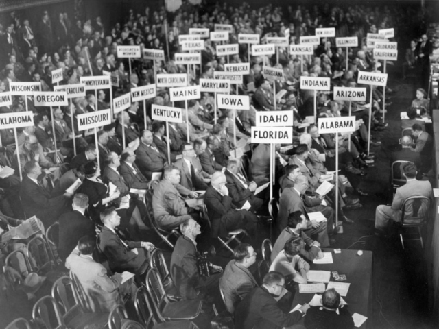 Voting delegates from 48 states and Puerto Rico consider the resolutions that determine the policies of the American Farm Bureau Federation for 1954 during the AFBF annual meeting held in New York City. Oklahoma's delegation is seated in the left foreground.