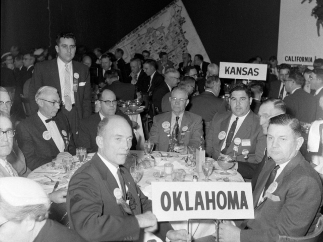 "Forty-six Oklahomans attended the 37th annual meeting of the American Farm Bureau Federation in December 1955, including Oklahoma Farm Bureau's four voting delegates: President Lewis H. Munn; Harold Davis, Roff; Mart Fowler, Stigler; and W.M. Deck, Balko. During the business session, delegates considered several resolutions concerning a variety of issues, including the Agricultural Act of 1954, the adoption of a ""soil bank"" policy to stockpile fertility in the soil for use in emergencies, states' rights and more."