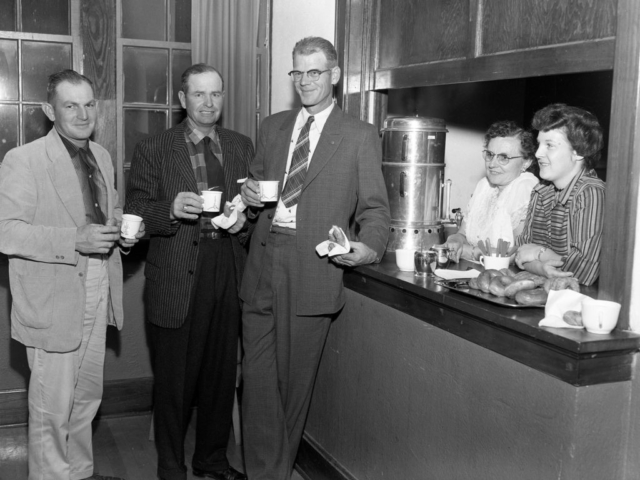 D.G. Meier Jr., Bennie Tice and Orval Swain enjoy coffee and doughnuts provided by Mrs. O.E. Redden and Mrs. Meier after the business session of Blaine County Farm Bureau's annual meeting in 1957. The event was also attended by a number of foreign agricultural information workers who were touring the nation to study American information and  extension services.