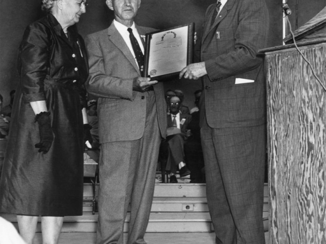 In 1957, the State Fair of Oklahoma asked Farm Bureau to participate in a special Farmers Day at the fair and conduct county contests to select a Golden Anniversary Farm Family. The award was designed to recognize the type of rural people who built Oklahoma in its first 50 years of statehood. The contest was limited to those who had lived on an Oklahoma farm since 1907. A total of 45 county winners were reported by county Farm Bureaus in the contest. Pictured here is Gov. Raymond Gary (right) presenting a gold and silver plaque to the overall winner of the contest, Mr. and Mrs. Fred Graumann, in the bandshell of the State Fair of Oklahoma on September 26, 1957. This was the beginning of a Farm Family award program that continues to today.