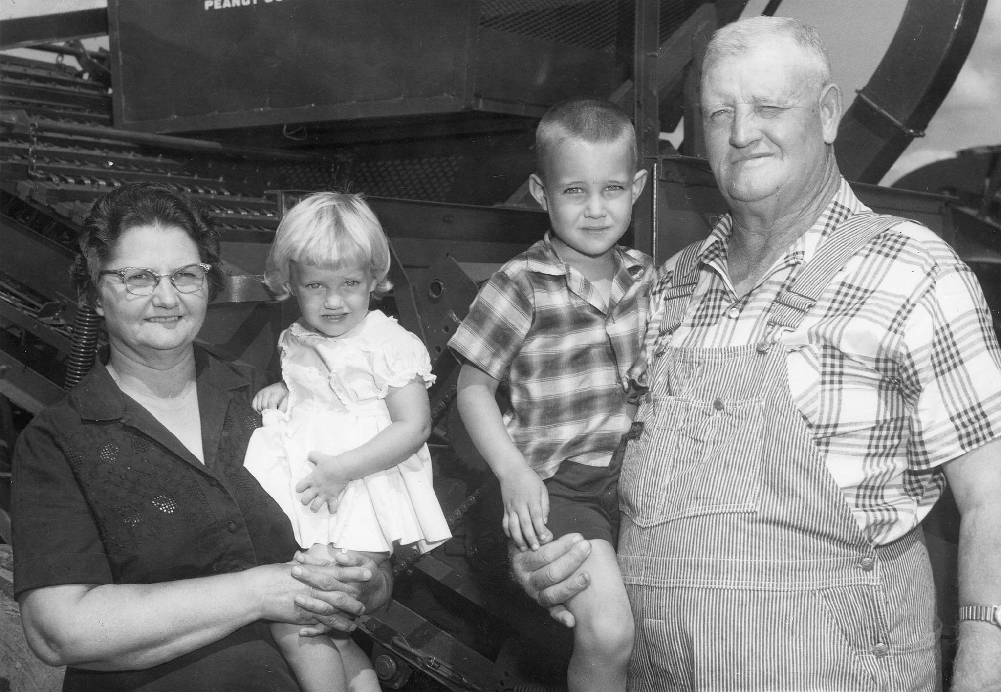 For the 1963 Farm Family award, the OKFB Women designed the contest to honor the state's pioneer farm families who fought floods, dust bowl days, and the depression in order to remain on the farm. One of the requirements was that the family, or the family's parents, must have farmed in Oklahoma prior to 1900. The George Lasley family from Eakley was the winner of this special Oklahoma Pioneer Farm Family of the Year award. Both of the Lasleys' parents originally came to Oklahoma in covered wagons in 1899. In the photo is Mr. and Mrs. Lasley, with the two youngest of their eight grandchildren, Gay and Lloyd.
