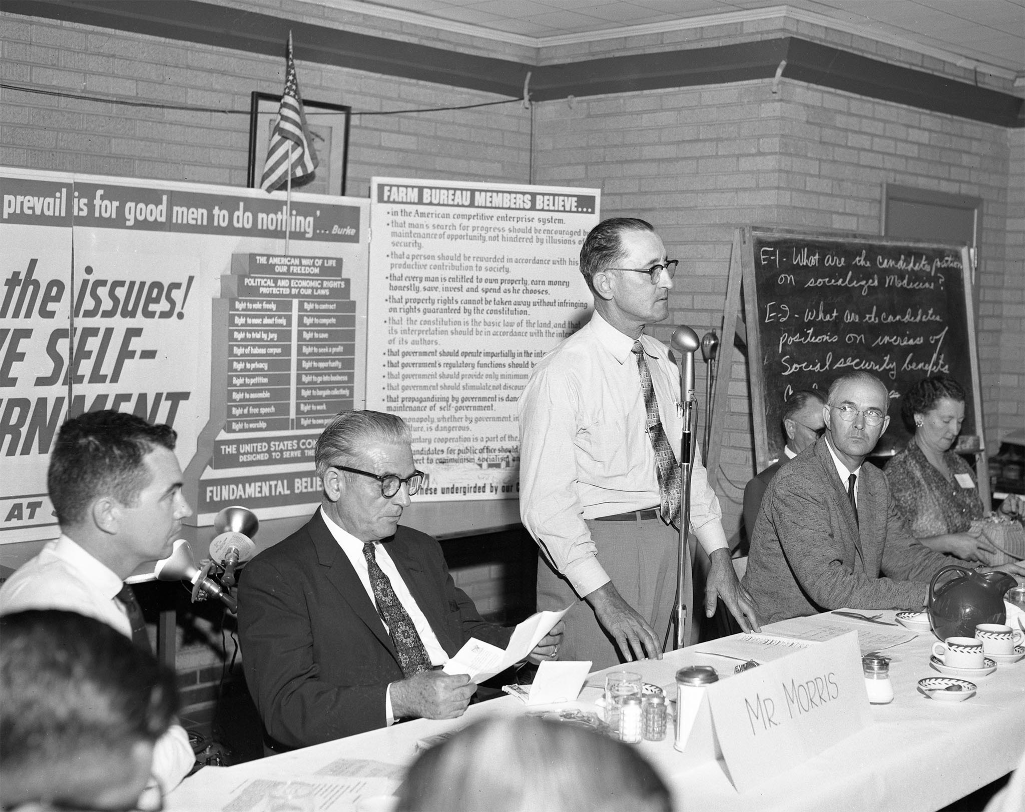 On July 10, 1958, members of Farm Bureau counties in western Oklahoma held this Meet the Candidate forum with two runoff candidates for the democratic nomination for congressman. Congressman Toby Morris (second from left) and challenger Victor Wickersham (second from right) were guests of 100 leaders from 17 western counties of Oklahoma's Congressional District 6, shown here with OKFB President Lewis H. Munn (at microphone). The candidates were quizzed about their beliefs on 13 different issues and government philosophies in order to compare them against Farm Bureau policy.