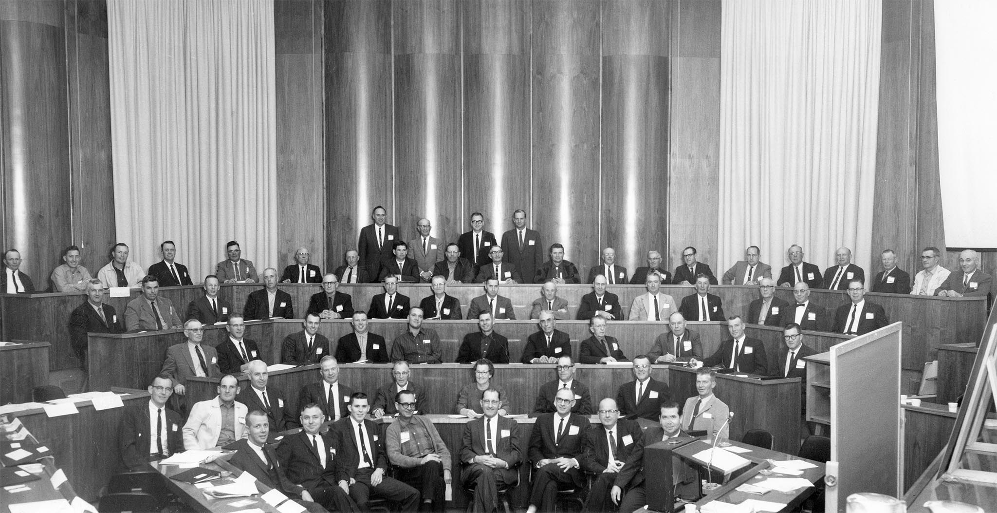 In March 1965, the OKFB Board appointed a 22-member program study committee to assess the functionality of the organization and find ways to better serve the needs of members. A special conference of county presidents, pictured here, was then held at the Center for Continuing Education at the University of Oklahoma to analyze the recommendations. After conference attendees endorsed the report, a special session of voting delegates approved the recommended proposal to increase Farm Bureau membership dues to a minimum of $15 in order to finance a portion of the expanded program.