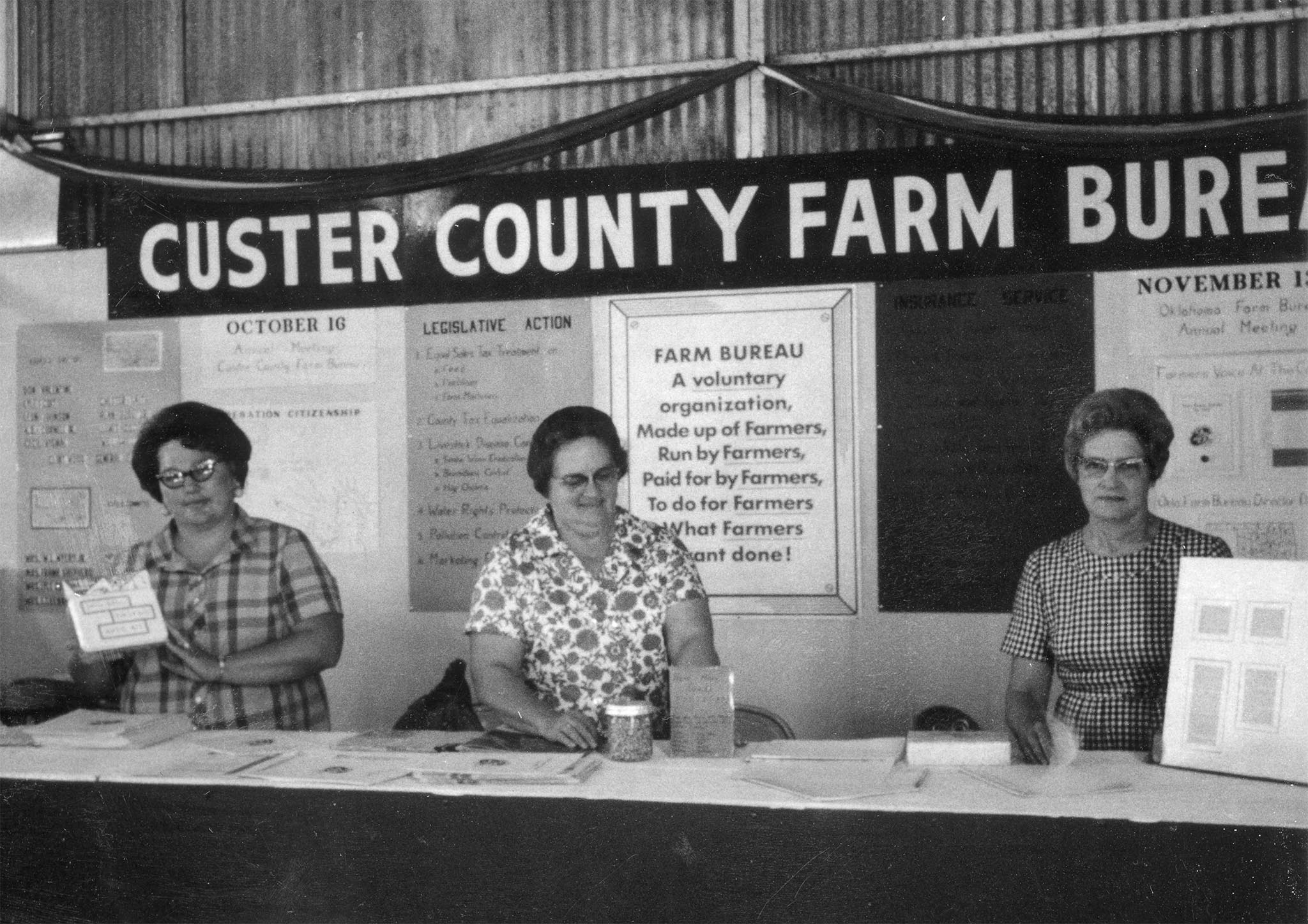 This fair booth was in Custer County in 1967. Tending to the booth are Mrs. Steward Barrick, Mrs. Con Burgtorf and Mrs. Tony Murray, who placed special emphasis on the legislative and policy development programs of Farm Bureau and information aids used to keep members informed.