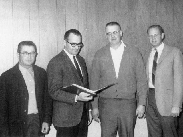 In 1968, Texas County was the focal point of a silage survey conducted by the American Agricultural Marketing Association as part of a multi-state study of silage marketing. Shown looking over some of the data gathered in the survey are Norman Hinds, Texas County Farm Bureau Board member; Tom Bennett, AAMA research staff member; Ronald Wagner, Texas County Farm Bureau President; and Virgil Higgins, Texas County Farm Bureau Board member.