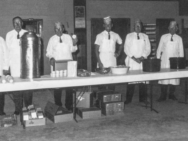 Noble County Farm Bureau Board members dish out the meal at a county annual meeting. Pictured are (left to right) Perry Patch, Homer Main, Oscer Mitchell, Bob Bolay, Walter Hasselwander, Sam Bolay and Alfred Graves, preparing to get the meal underway. Hasselwander was a special insurance agent in the county.