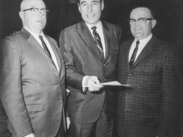 This 1968 photo, taken at the Garvin County Farm City dinner, features Dr. Robert B. Kamm, President of Oklahoma State University (center), discussing current issues with A.J. Chapman, Garvin County Legislative Chairman (left), and O.W. Parker, Garvin County President. Kamm was the principal speaker for the 300 people who attended the dinner.