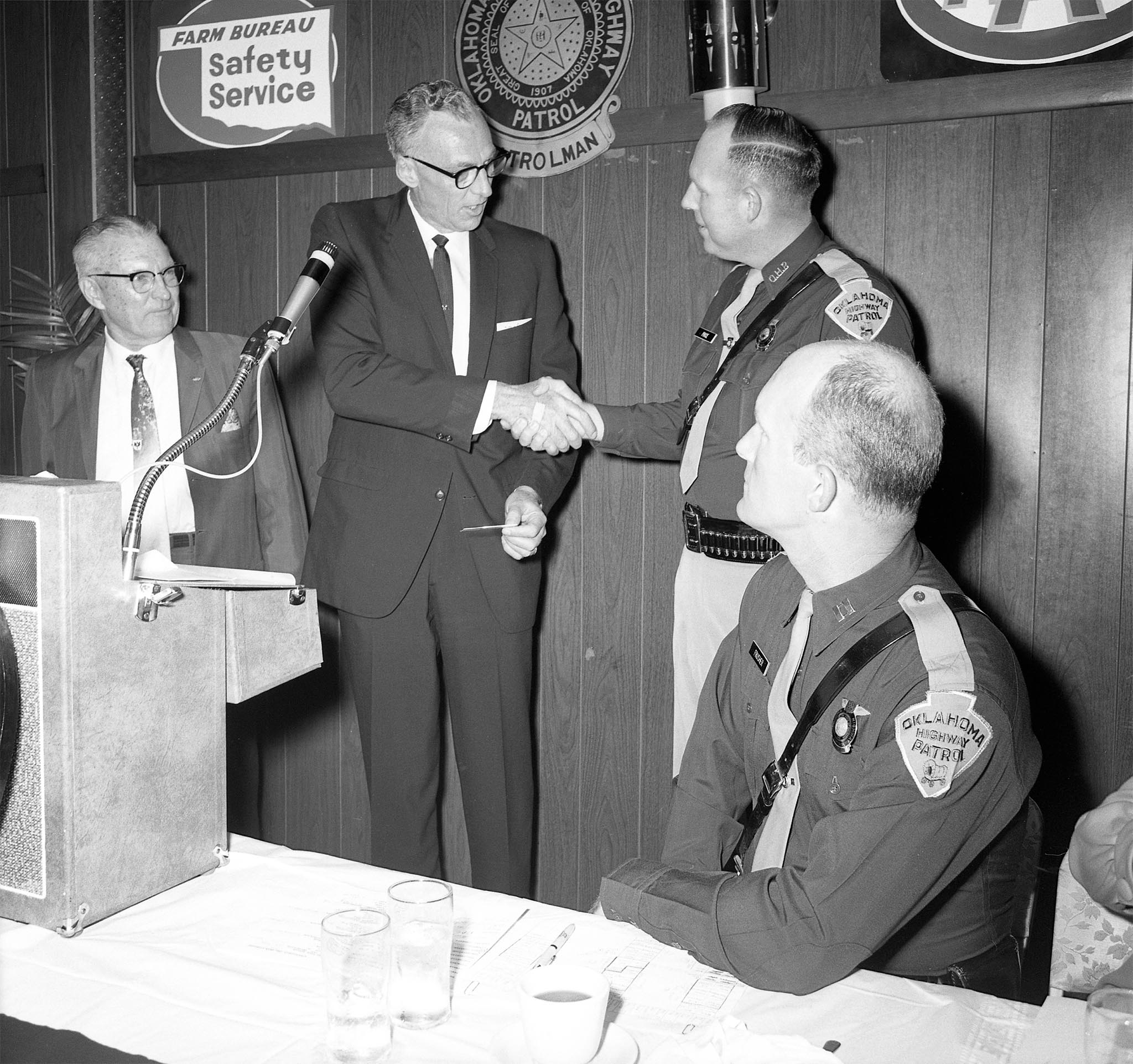 "Ted Payne, Oklahoma Farm Bureau Safety Director (second from left), and Col. L.M. Tidd of the American Automobile Association (left), thanks Trooper Bill Price (second from right) and the Oklahoma Highway Patrol for being a part of the ""Learn and Live"" program just before the show winners were presented. The 1968 program involved five high schools located in central Oklahoma, including schools in Guthrie, Chickasha, Moore, Shawnee and Putnam City. Teams participated in the quiz-based television show by answering questions taken from the Oklahoma traffic code."