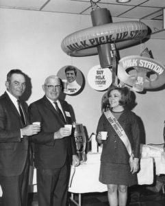 Emmett Carter of Purcell, Vice President of American Dairy Association, and Roy Counts of Dover, Secretary of Milk Producers Inc., take a milk break with Oklahoma Dairy Princess Quinetta Beagle of Arnett during a meeting in Oklahoma City in 1969.
