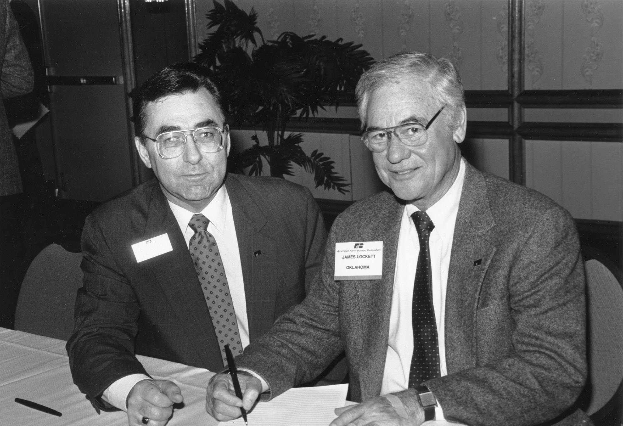 In this 1990 photo, James Lockett, OKFB President (right), pictured with American Farm Bureau Federation President Dean Kleckner, signs a Farm Bureau petition favoring reduction of the capital gains tax.