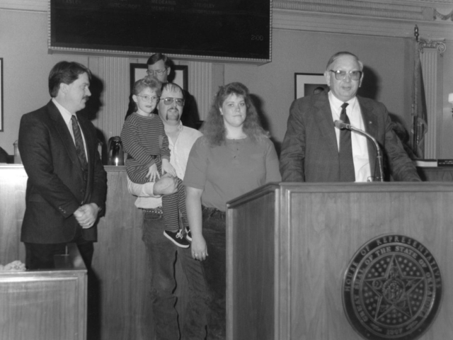 "The importance of young farmers and ranchers was recognized in this 1990 photo, in which Rep. Jack Begley (right) presented a citation to the Oklahoma Farm Bureau Young Farm Family of the Year, Texas County's Monte and Bobbi Smith. Begley read the citation recognizing the family to the House chamber while Speaker of the House Steve Louis (in background) and OKFB's Director of Governmental Relations Dennis Howard (left) listened. The lawmaker told his counterparts he wanted them to meet an ""endangered species – young farmers in Oklahoma."" The Smith family owned a diversified farm and ranch near Texhoma, where they raised cattle and grew wheat, alfalfa and sudangrass."