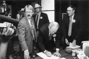 In 1994, Oklahoma Farm Bureau President Eldon Merklin attracted media coverage as he became the first person to sign a petition that would give taxpayers control over ad valorem tax levels. OKFB was part of a coalition that supported placing the Property Owners Protection Act on the ballot. Later, petitions were signed at county Farm Bureau offices. Also pictured at the signing event was Oklahoma Taxpayers Union President Dan Brown, OKFB Board Member Joe Mayer and coalition spokesman Jim Williams.