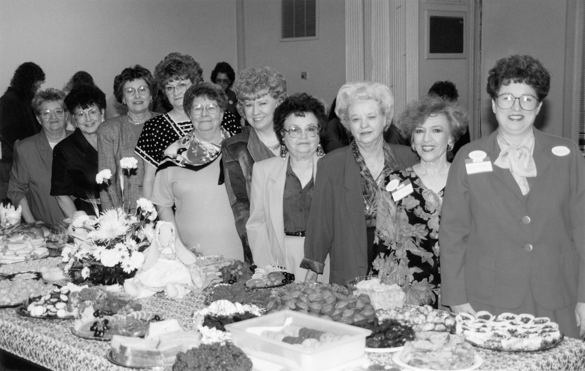 One of the most popular events hosted by the Oklahoma Farm Bureau Women's Committee is the Farm City Festival. Women from across the state bring home-prepared food, featuring ingredients produced in Oklahoma, to the Oklahoma State Capitol during the legislative session to educate lawmakers and their staff about the Oklahoma agriculture industry. Here, members pause briefly behind their decorated table containing homemade foods before long lines form for the Farm City Festival in 1994. During the event, more than 500 individuals registered in the guest book. Committee members include (left to right): June Kliewer, Doris Lee Howard, Juanita Bolay, Yvonne Phelps, Beverly Delmedico, Sue Jarvis, Chairman Nellie Fern Nelson, Helen Keller and Sarah Henson.