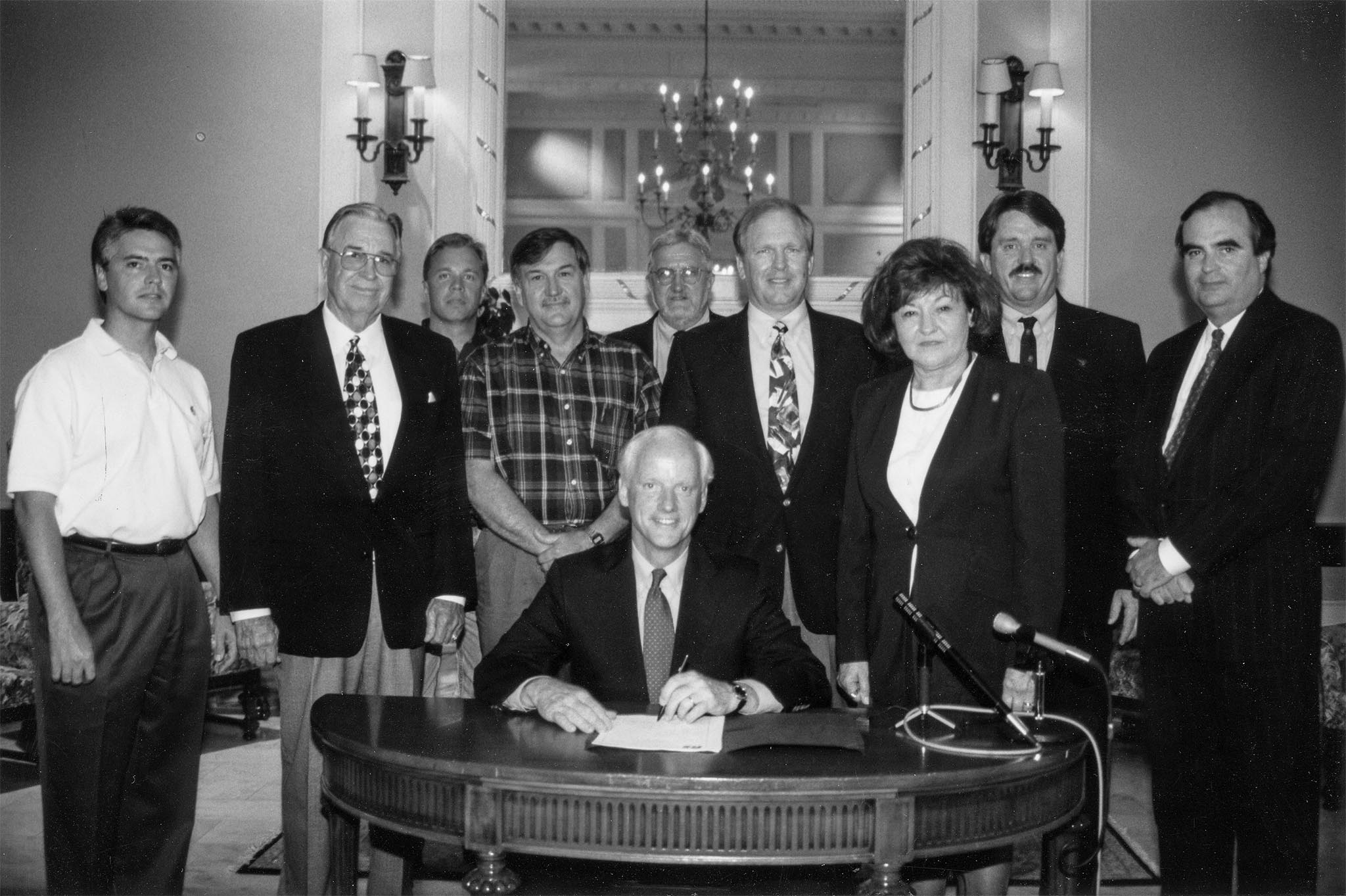 This photo was taken June 12, 1998, as Gov. Frank Keating's signature on Oklahoma's estate tax reform bill drew a large crowd of interested witnesses. Attending the ceremony in the Oklahoma State Capitol's Blue Room were (left to right) OKFB General Counsel Richard Herren, OKFB President Jack Givens, OKFB Executive Director Matt Wilson, Mason Mungle, Rep. Larry Ferguson, Sen. Owen Laughlin, Rep. Mary Easley, Agriculture Commissioner Dennis Howard, and Director of State Finance Tom Daxon.