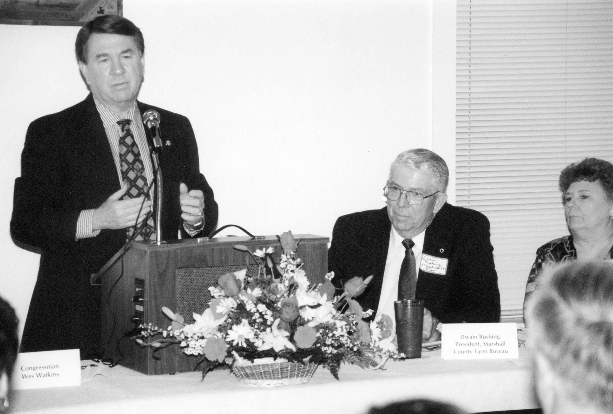 Almost 80 Farm Bureau members from five counties in southeastern Oklahoma assembled in Madill on April 6, 1998, to host U.S. Rep. Wes Watkins. It was the first time for Marshall County Farm Bureau to host a special legislative meeting featuring the third-district U.S. congressman. Marshall County Farm Bureau President Dwain Rushing listened as Rep. Watkins briefed leaders on some of the upcoming issues that would face Congress.