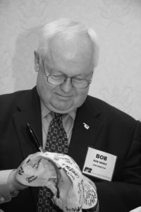 """Oklahoma Farm Bureau Board Member Bob Drake of Murray County signs an OKFB cap that was passed around to members at the 2009 State Resolutions Committee meeting, showing support for the American Farm Bureau Federation's """"Don't cap our future"""" campaign. The campaign rallied against a proposed """"cap and trade"""" scheme of environmental controls that was being proposed in Congress. Two signed caps were sent to Washington, D.C., to show OKFB support for the campaign, one of which was used on the U.S. Senate floor by Sen. Jim Inhofe during debate on the bill."""