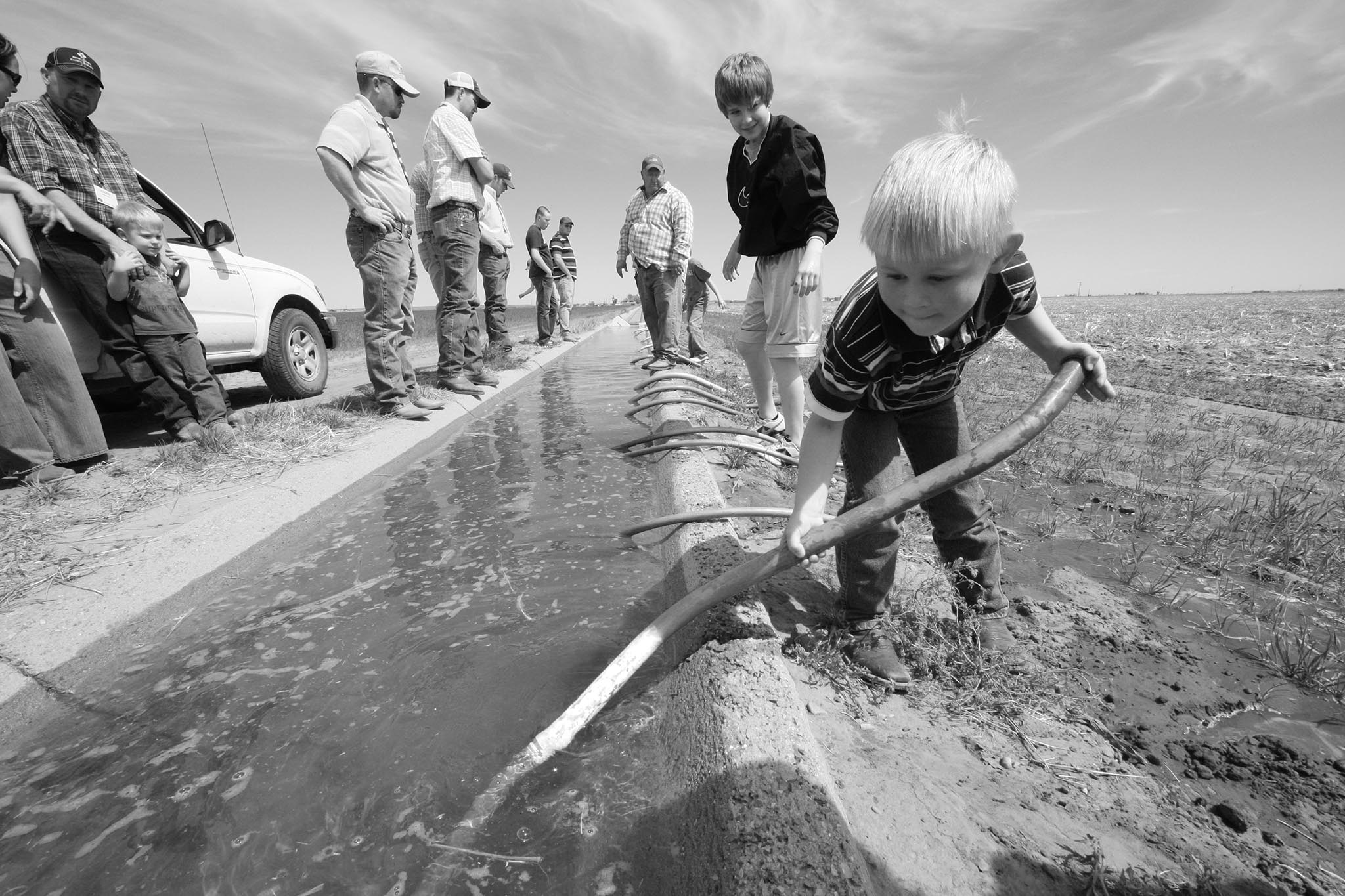 Here, a young Ryan Taylor of Payne County tries his hand at setting a siphon tube in the Lugert-Altus Irrigation District as part of a 2011 OKFB Young Farmers & Ranchers tour.