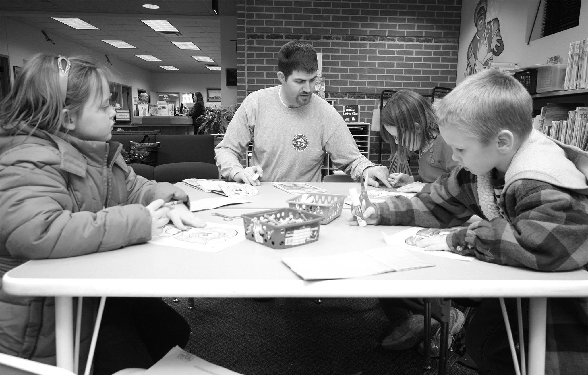 In this January 2012 photo, Major County Farm Bureau Young Farmers & Ranchers member Clint Wilcox (center) helps local children color a farm-themed picture at a local library. County YF&R members also read agricultural books, played farm-themed games and prepared a snack for local grade-school students to help them understand the importance of agriculture in their local community of Fairview and beyond.
