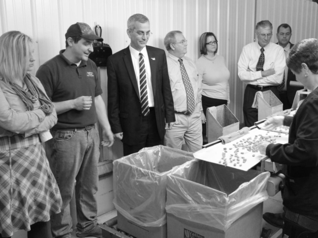 Oklahoma Farm Bureau member Josh Grundmann (second from left) shares the process of cleaning and shelling pecans with the Oklahoma State Board of Agriculture during a tour in 2013. The Grundmann family hosted the group at their business, Valley View Pecans near Earlsboro, to help educate board members about the pecan industry and issues pecan producers and processors face.