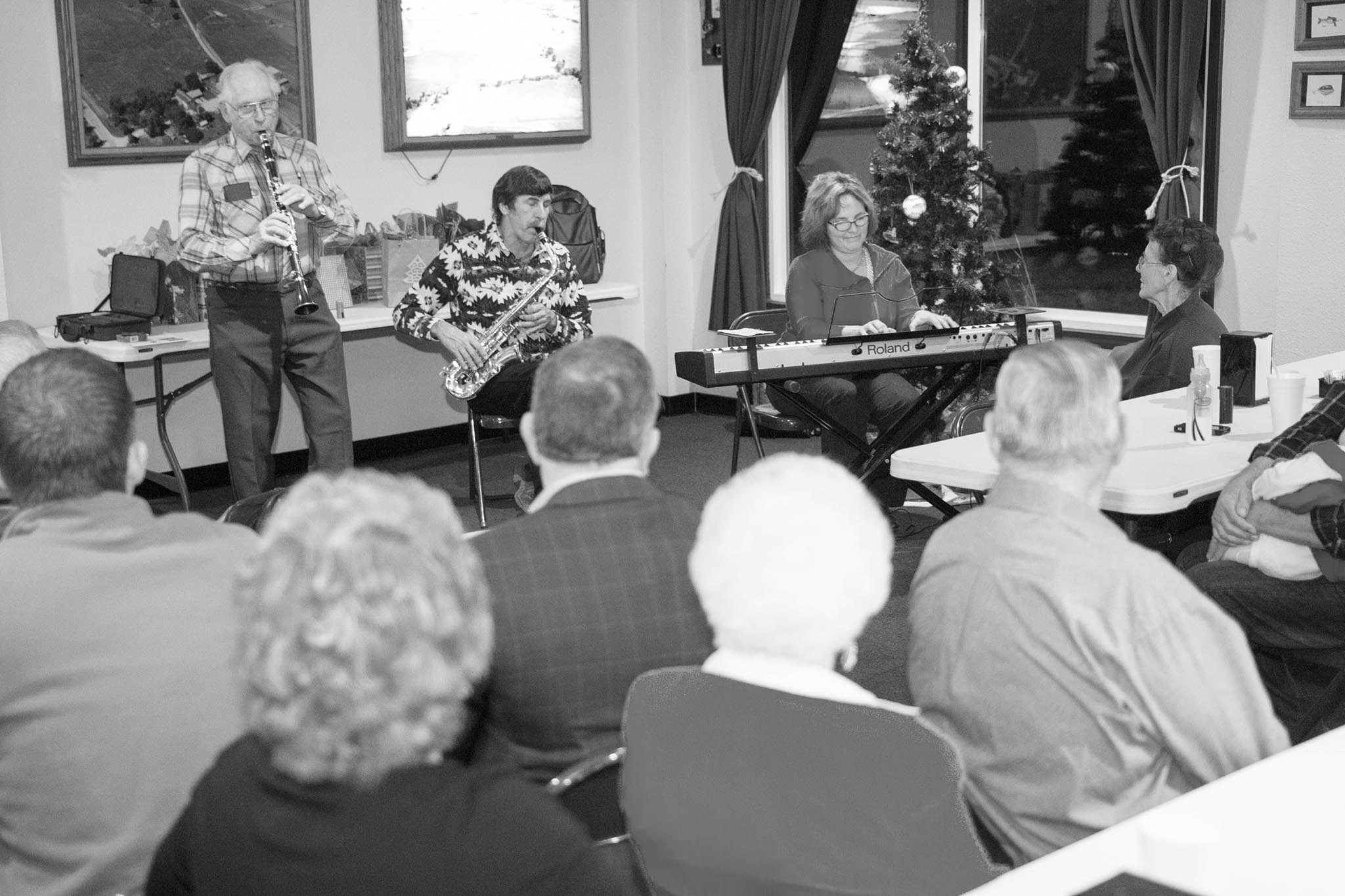 Here, Rogers County Farm Bureau members, including County President E.J. Snider on the clarinet entertain members during the county's annual Christmas party in 2014, which included a meal and a gift exchange.