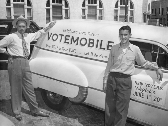 During Oklahoma Farm Bureau's get-out-the-vote campaign, the organization launched the Votemobile, a sound truck that toured the state spotlighting the dates for registration and voting. With the launch of the Votemobile, Buck Garvin (left) southeast district insurance fieldman, temporarily left his duties to pilot the Votemobile on its statewide tour. His helper on the tour was Leon Moore (right), a student at Northeastern State College in Tahlequah. The photo was taken at their first stop in Purcell.